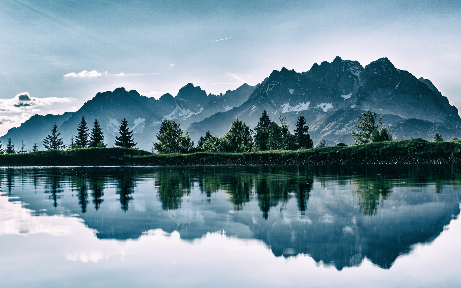 light shines over the mountains reflected in the calm waters of the lake.