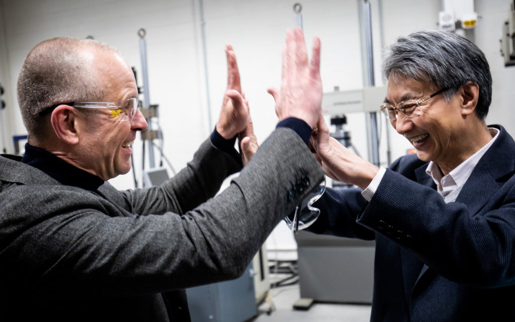 Volker Sick and Victor Li giving each other a high five handshake.